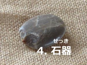 「4.せっき」の写真。薄いこげ茶色。全体として平たい楕円形だが石錘のような部分がある。