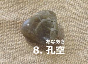 「8.あなあき」の写真。煤色、丸っこくいびつな三角形で孔やひびがある。